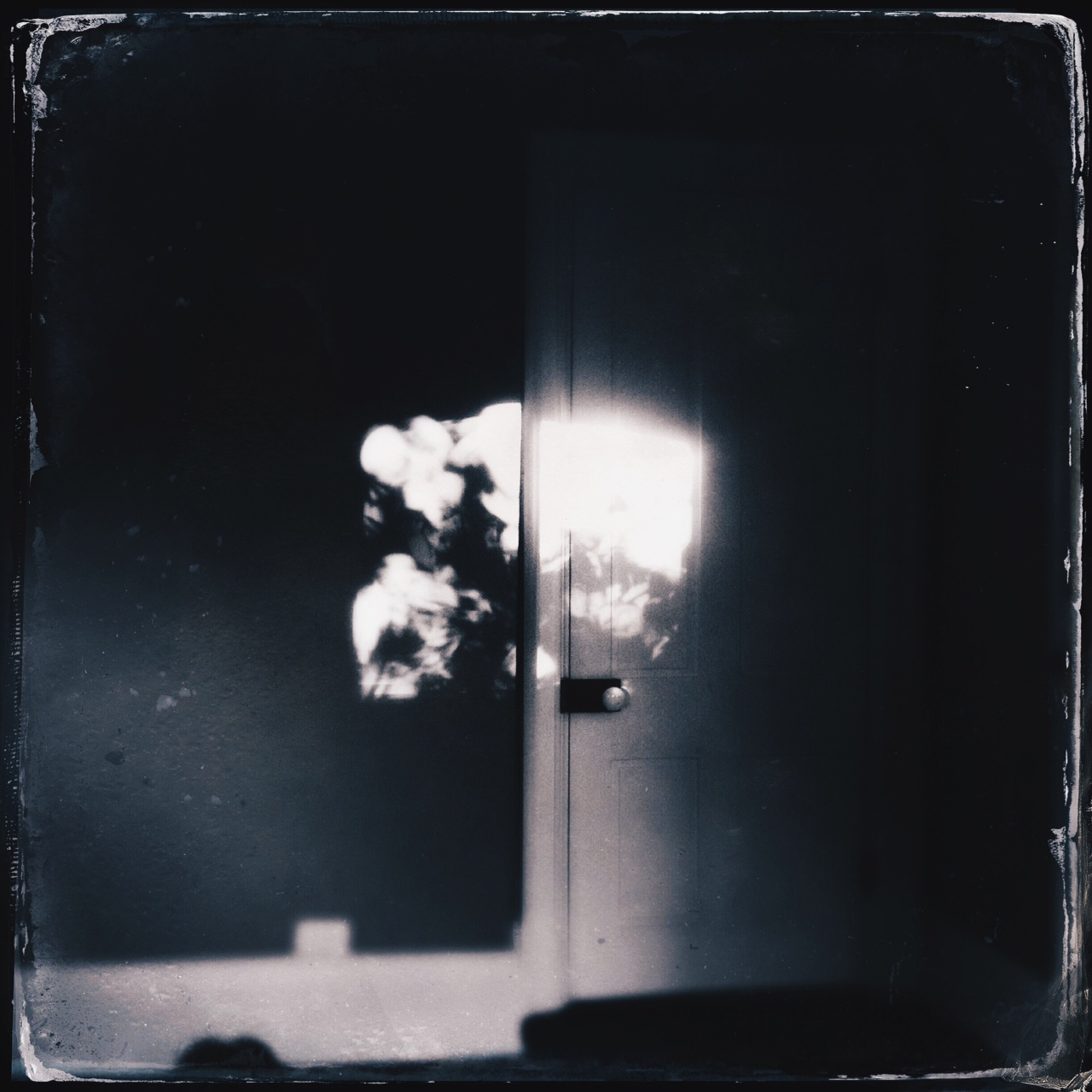black and white photo of light on a door