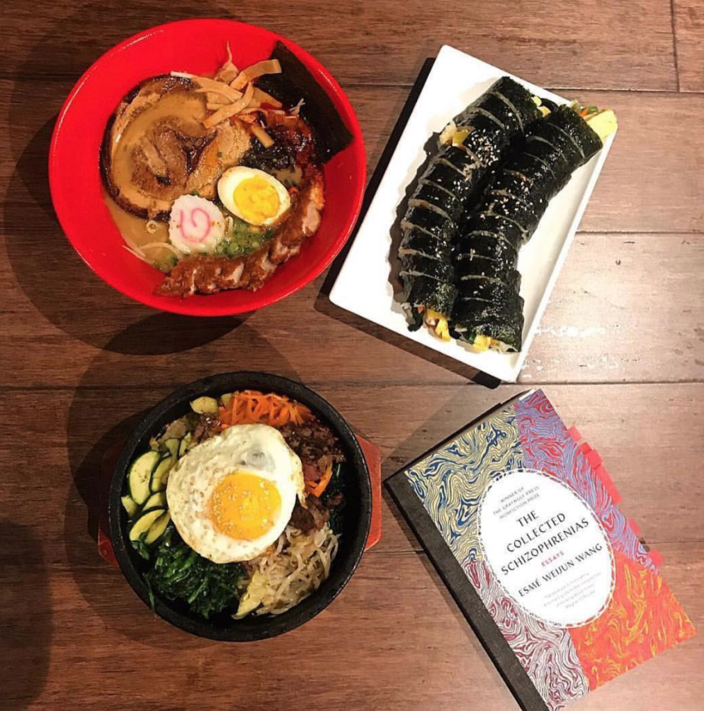 a copy of The Collected Schizophrenias with ramen and sushi on a wooden table